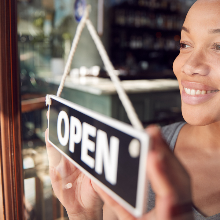 woman standing at glass door turning window sign to open